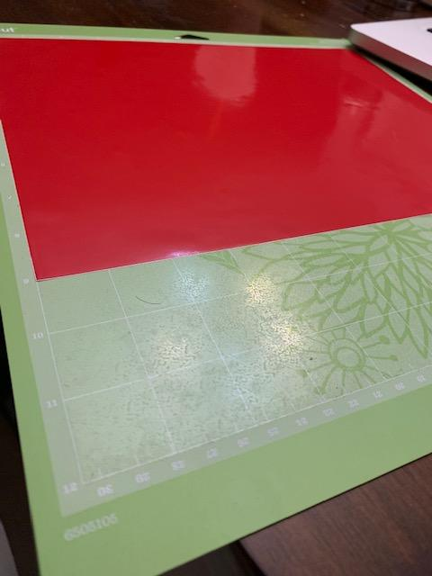 DIY Gift Cricut prepping the mat with red vinyl
