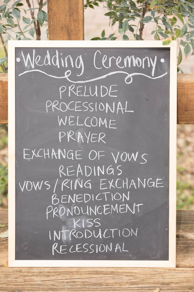 Chalkboard sign with wedding ceremony order of events written on it