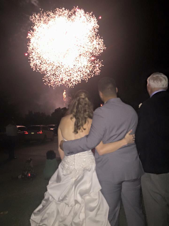 Bride and groom with father looking at fireworks during wedding reception