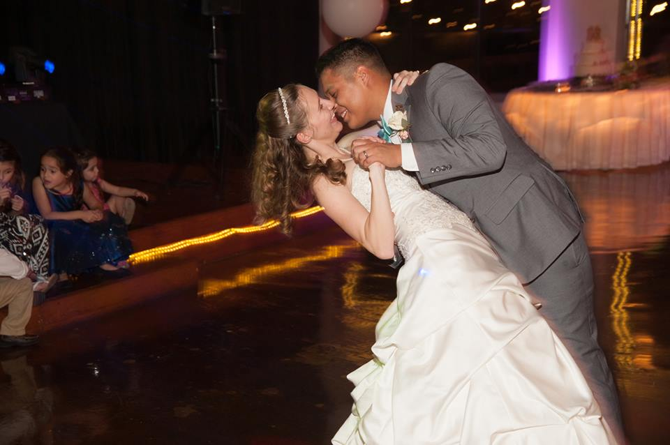 Bride and groom smiling having first dance at wedding reception
