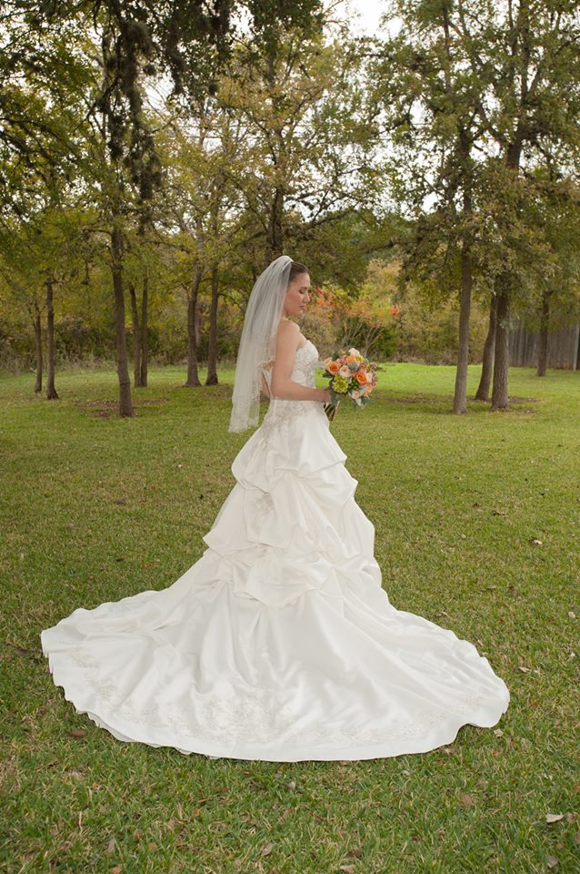 Bride in her wedding dress looking at bouquet of Fall flowers