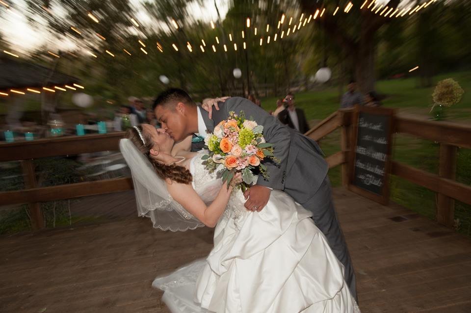 Groom dips bride on the deck overlooking the guests to share a kiss after saying I do on their wedding day
