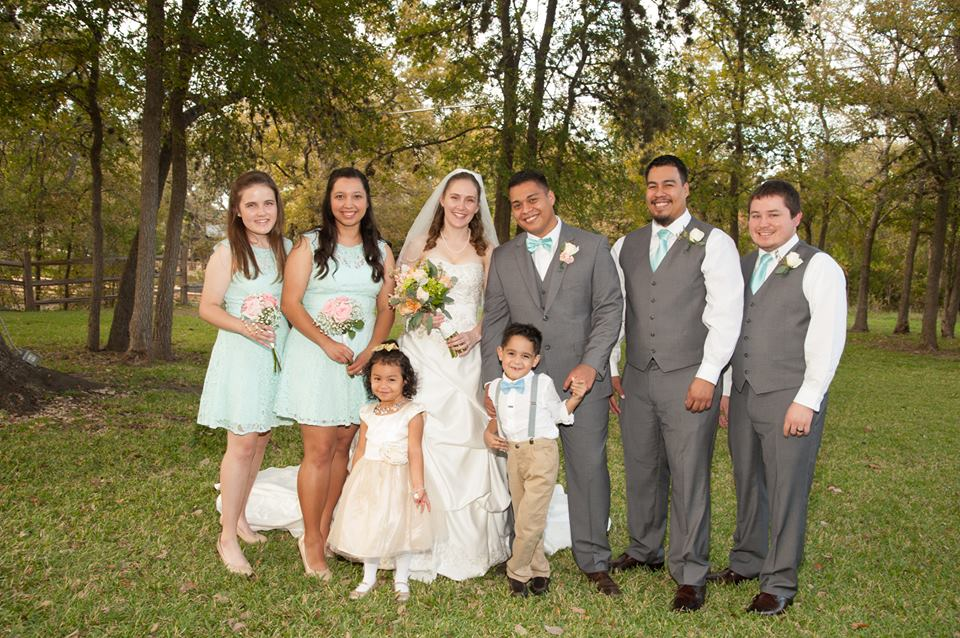 Wedding party of two women, two men, bride and groom, flower girl and ring bearer posing by fall foliage