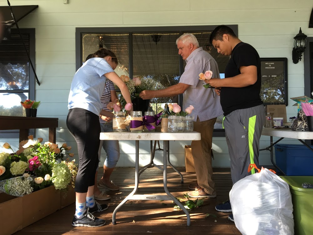 Future bride and groom, father, and matron of honor standing at a table outside wedding venue creating floral arrangements with mason jars